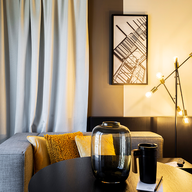 Aufnahme der Couch und des Tisches im Wohnbereich eines JOYN Serviced Apartments Basic