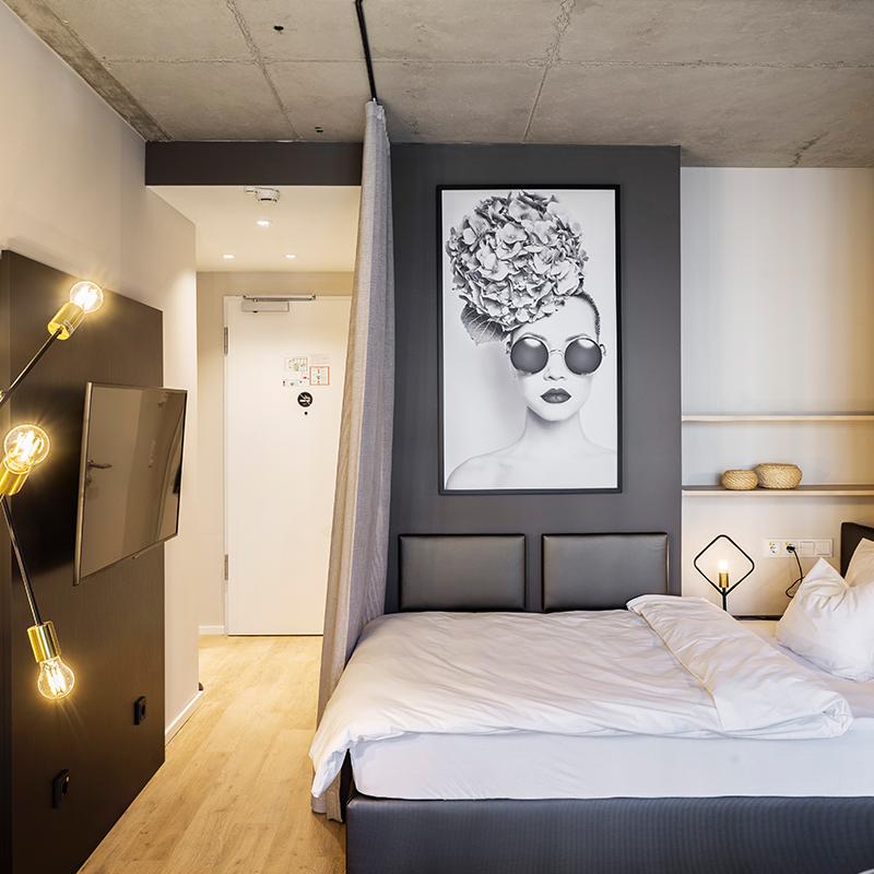 Einzelbett und Fernseher in einem JOYN Serviced Apartment Basic