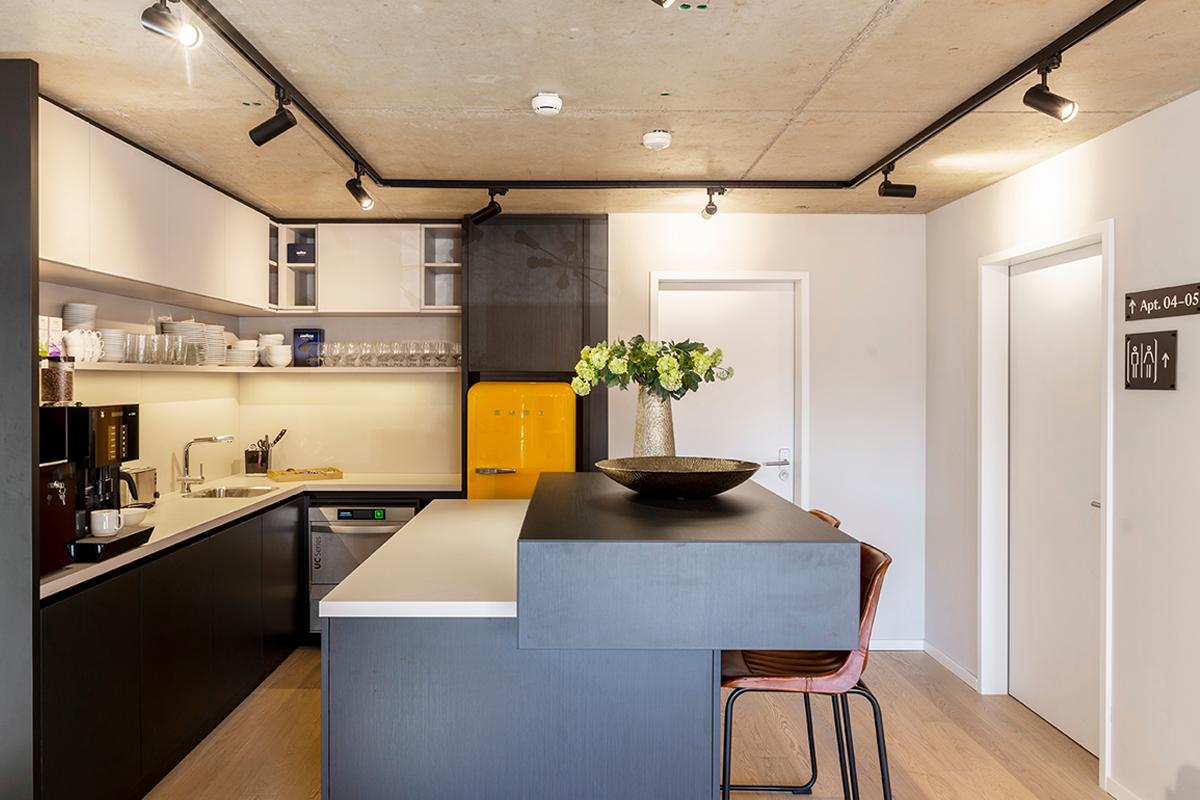 Küche mit vielen Annehmlichkeiten wie Kaffeemaschine, Kühlschrank und Spülmaschine in einer Community-Area