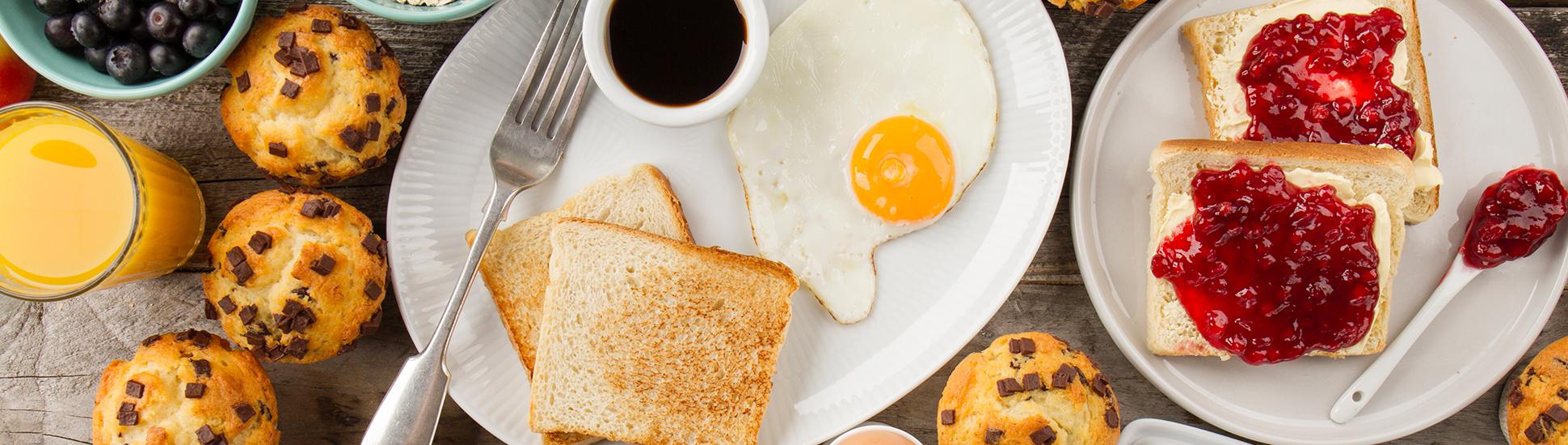Frühstück bestehend aus Saft, Beeren, Muffins, Spiegelei, Toast, Kaffee und Marmelade
