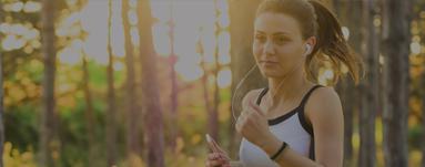 Frau joggt mit Kopfhörern durch den Wald