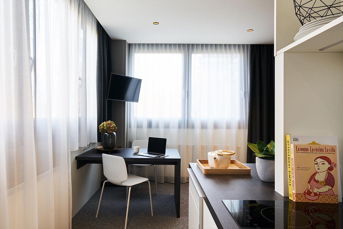 Kitchenette und Schreibtisch in einem JOYN Serviced Apartments
