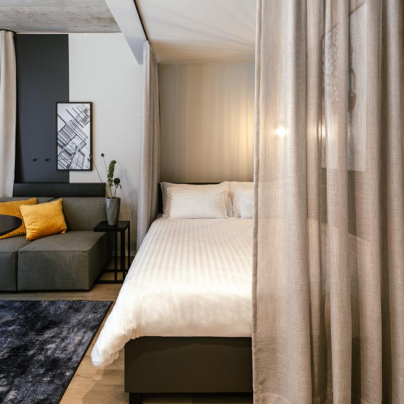Durch Vorhang halb verdecktes Doppelbett in einem JOYN Serviced Apartment Smart
