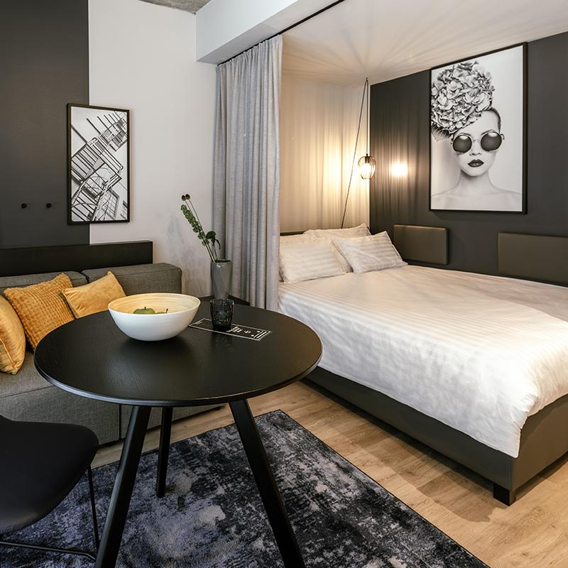 Einzelbett und Wohnbereich in einem JOYN Serviced Apartment Smart