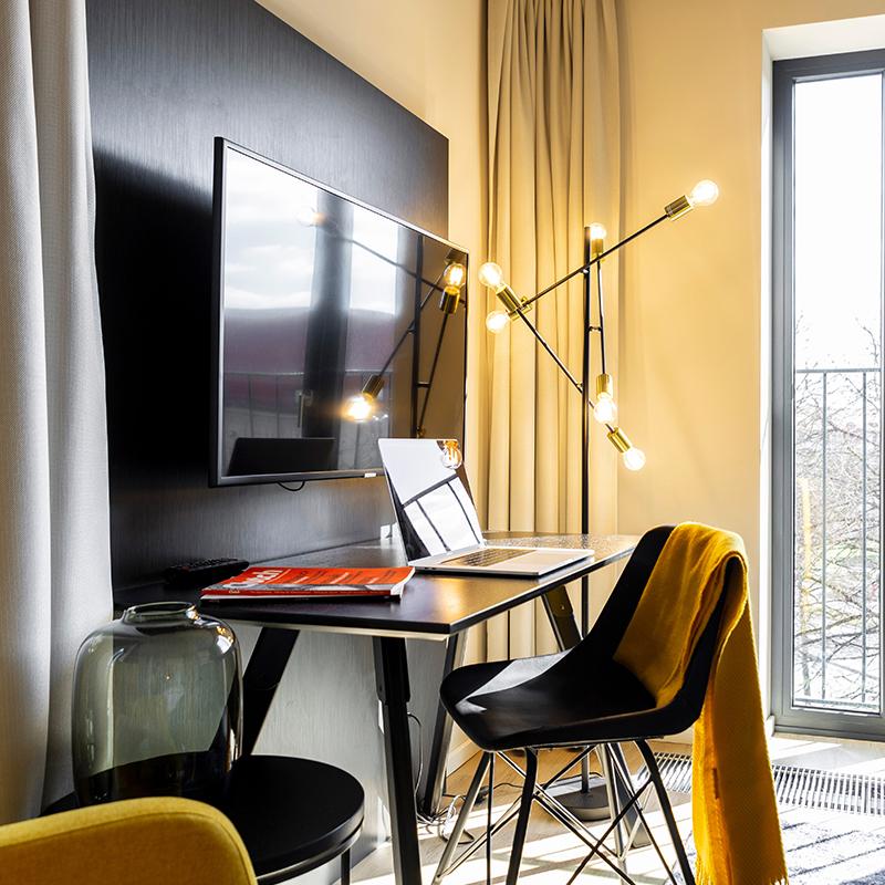Schreibtisch und Fernseher in einem JOYN Serviced Apartment Studios