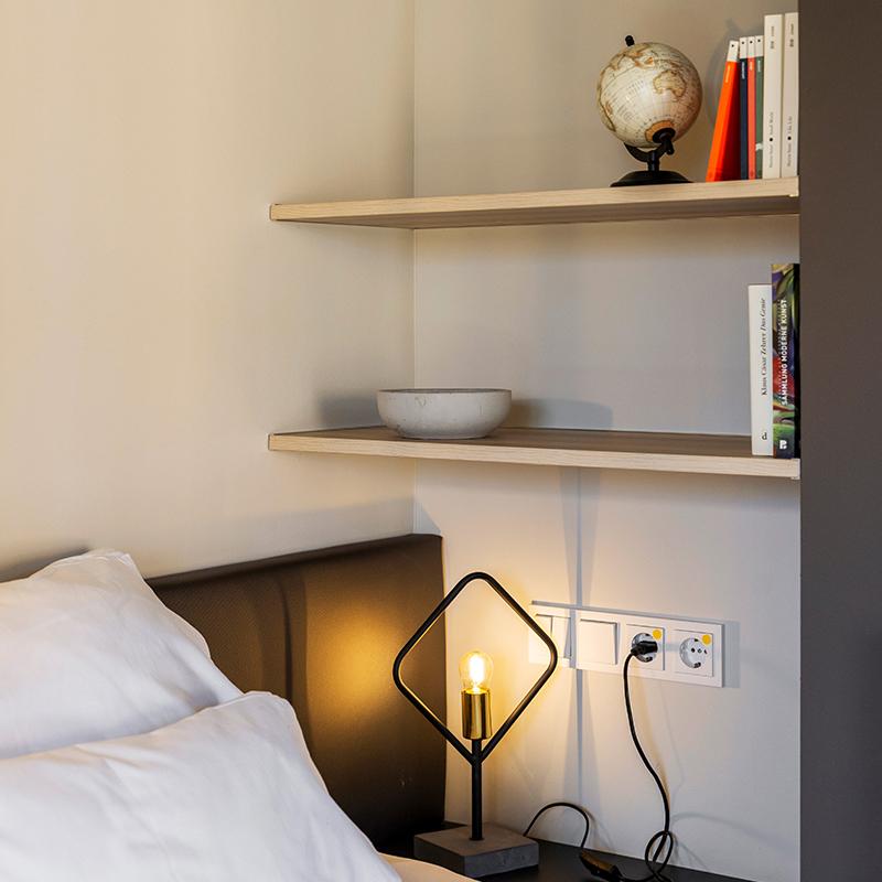 Aufnahme eines Regals befüllt mit Büchern und Dekoration in einem JOYN Serviced Apartment Studio