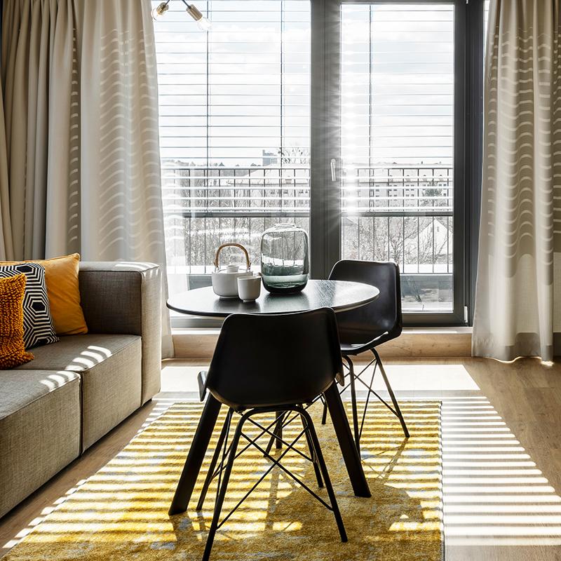 Wohnbereich eines JOYN Serviced Apartment Studio Plus ausgestattet mit Tisch, Stühlen und Couch