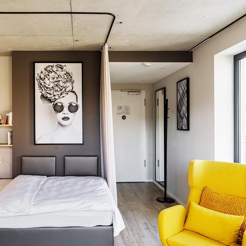 Bett und gelber Sessel in einem JOYN Serviced Apartment Studio