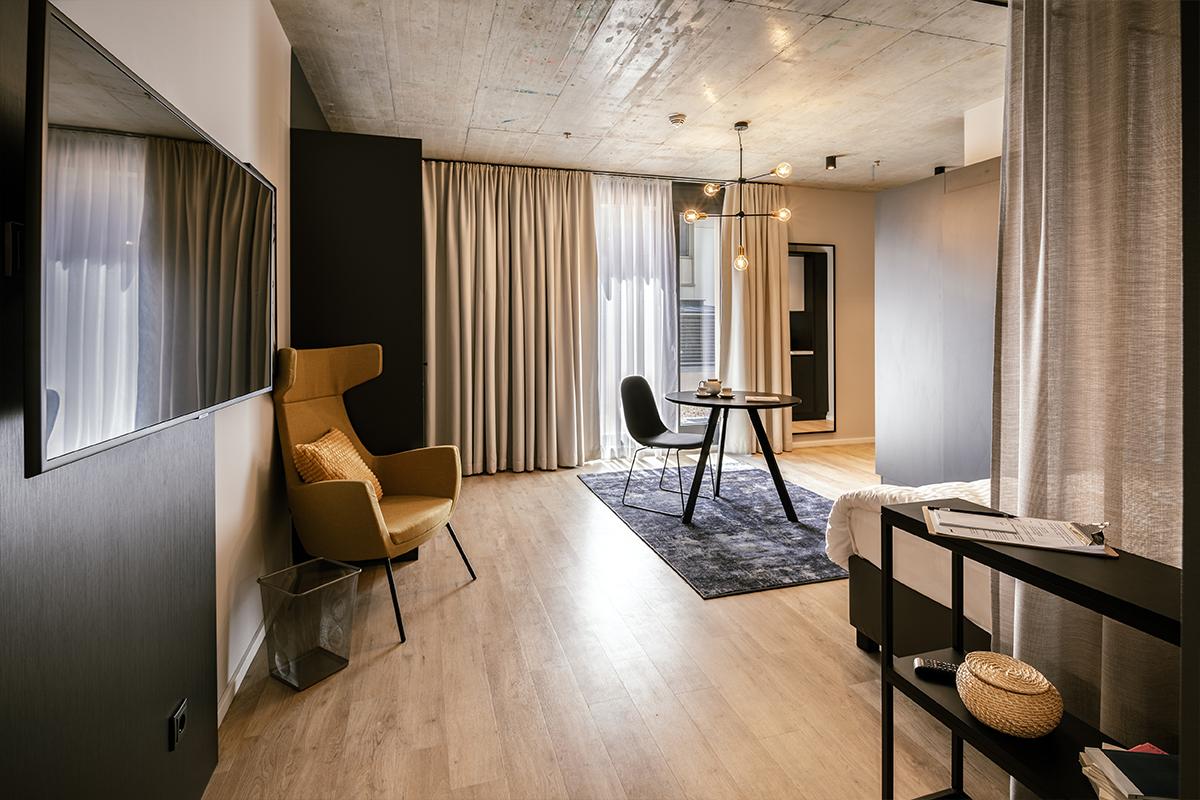 Stilvoller Wohnbereich mit Sitzecke eines JOYN Serviced Apartment Studio Plus