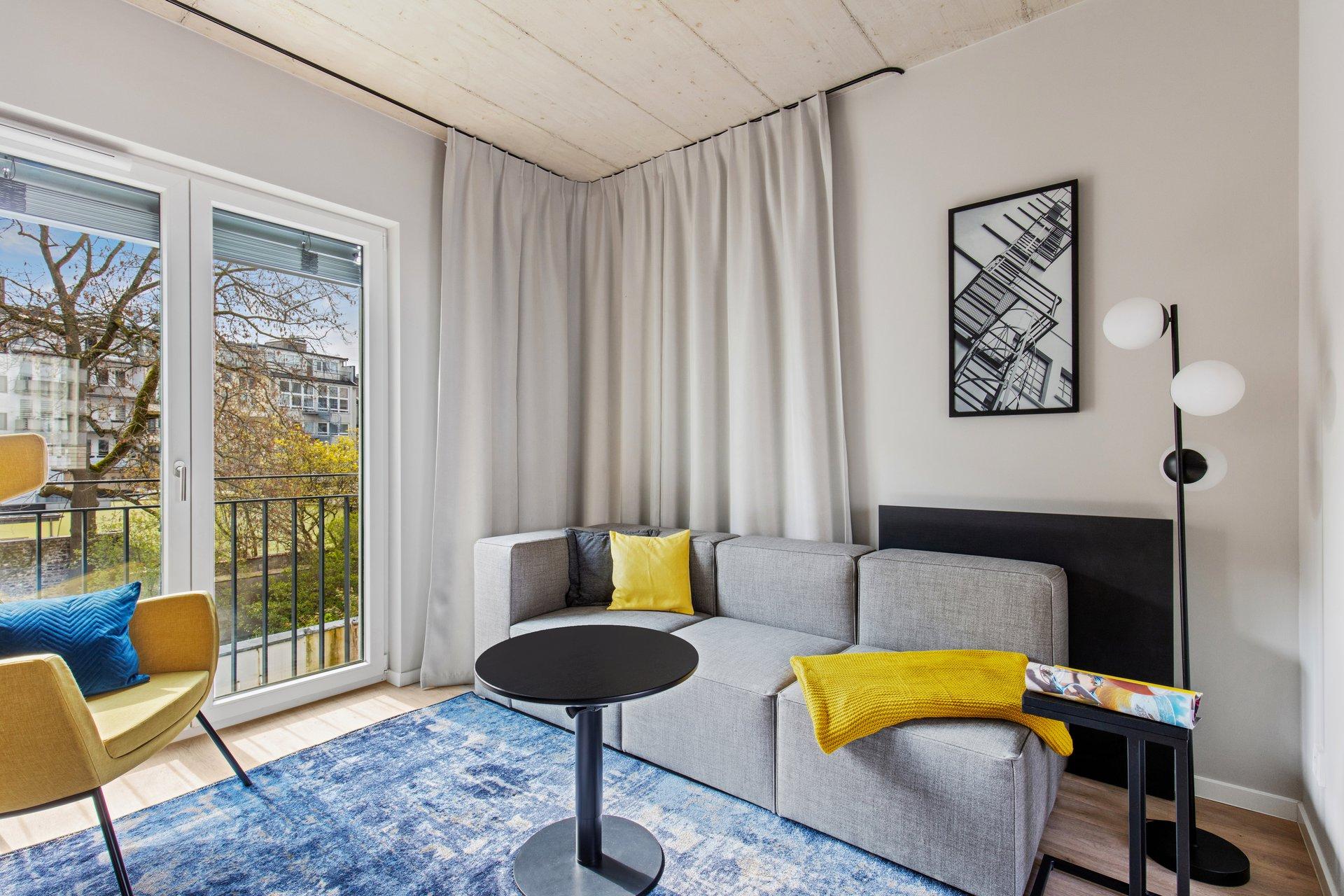 Moderner Wohnbereich ausgestattet mit Couch und tollem Ausblick im JOYN Serviced Apartment Düsseldorf