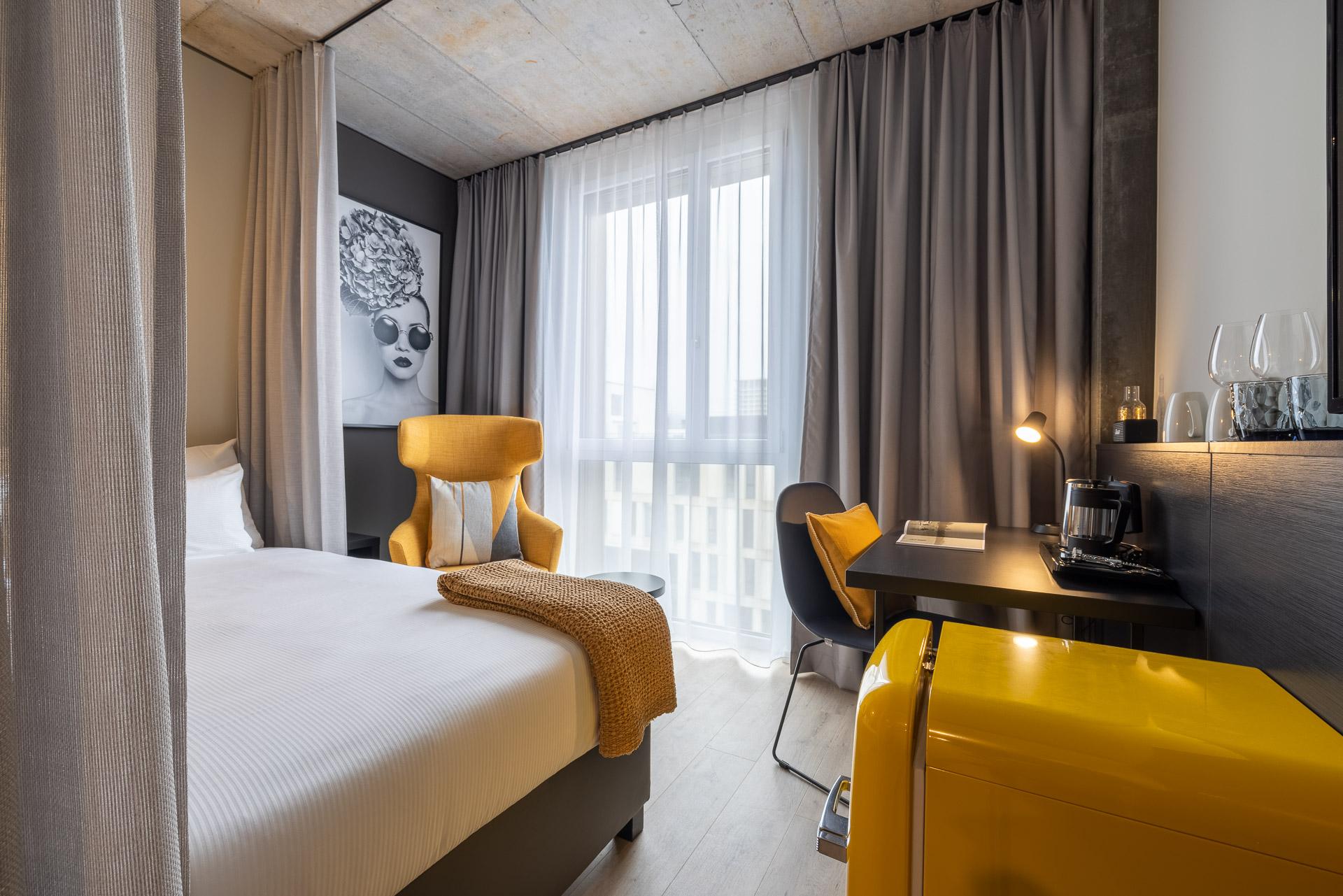 Basic Zimmer mit Bett, gelbem Sessel, Stuhl und Schreibtisch sowie gelben Kühlschrankenzeile