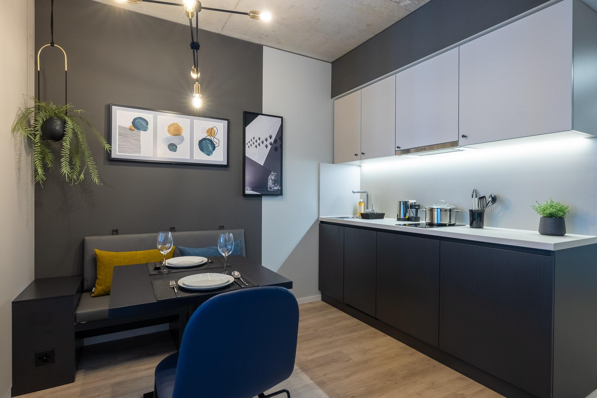 Studio Apartment mit Esstisch, Stuhl und Bank sowie Küchenzeile