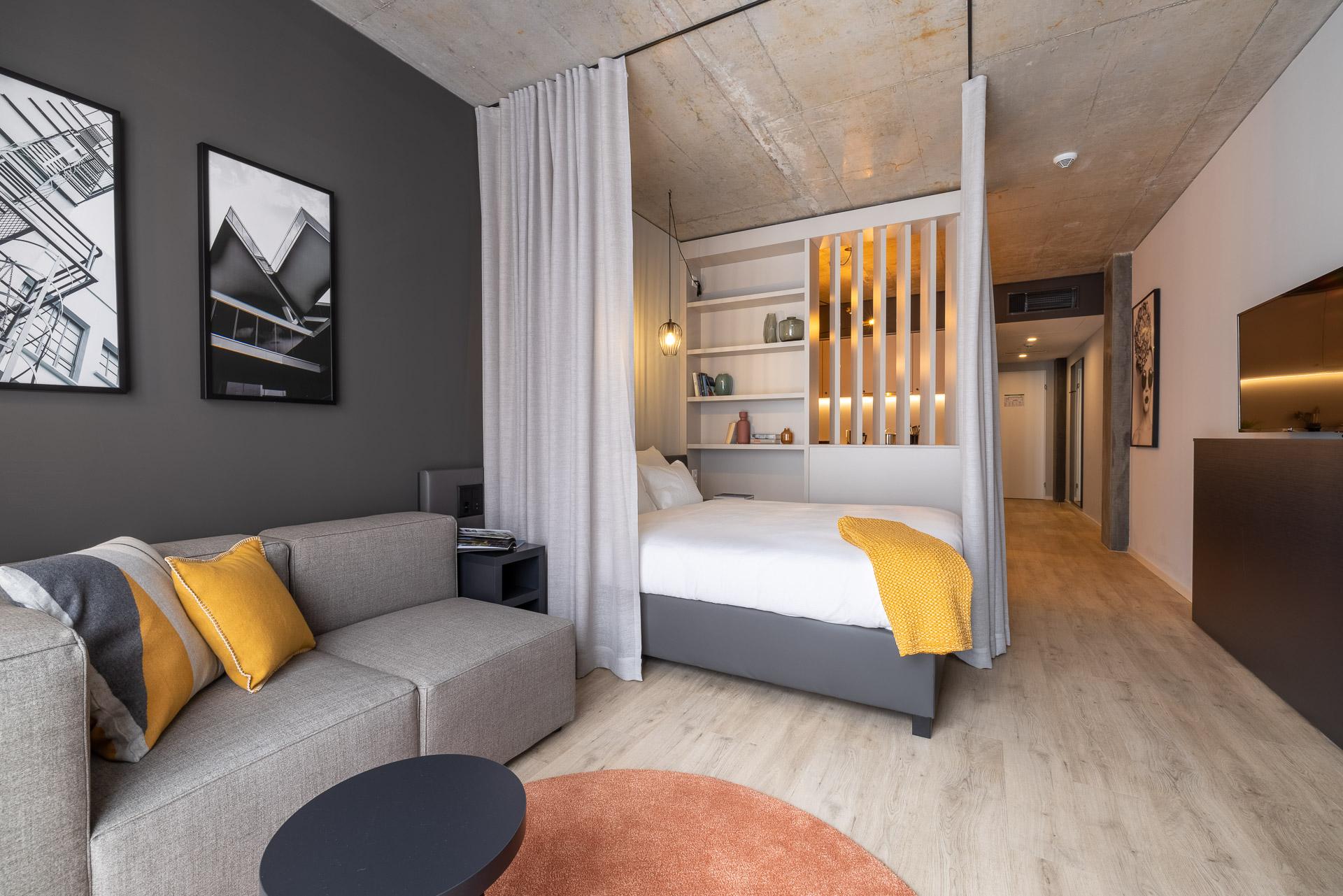Studio Apartment mit Sofa, Bett, Regal und Raumtrenner