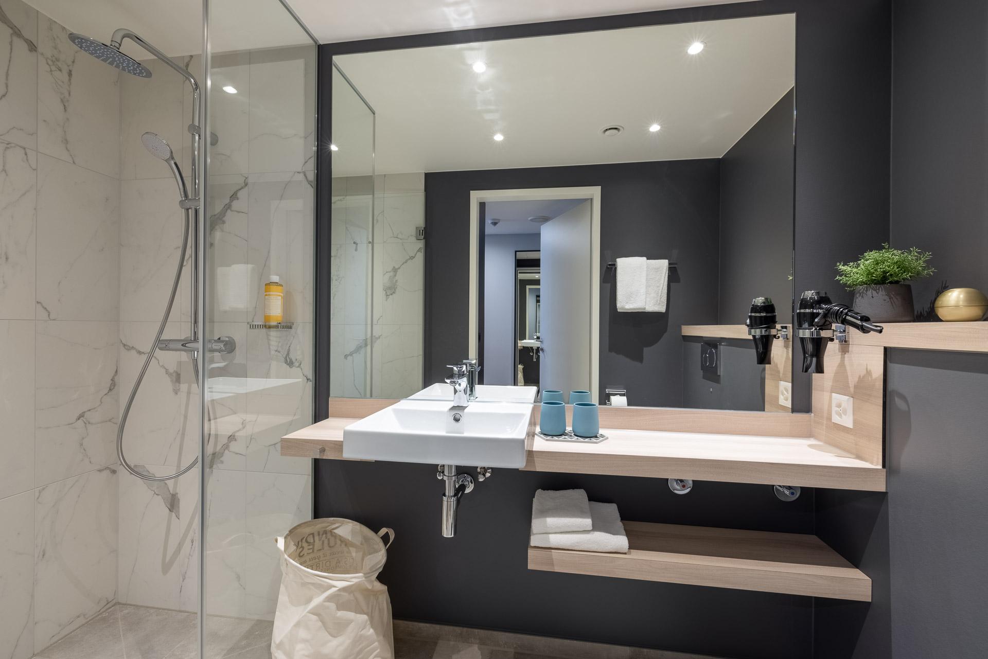 Badezimmer mit großem Spiegel, Ablagefläche und bodentiefer Dusche