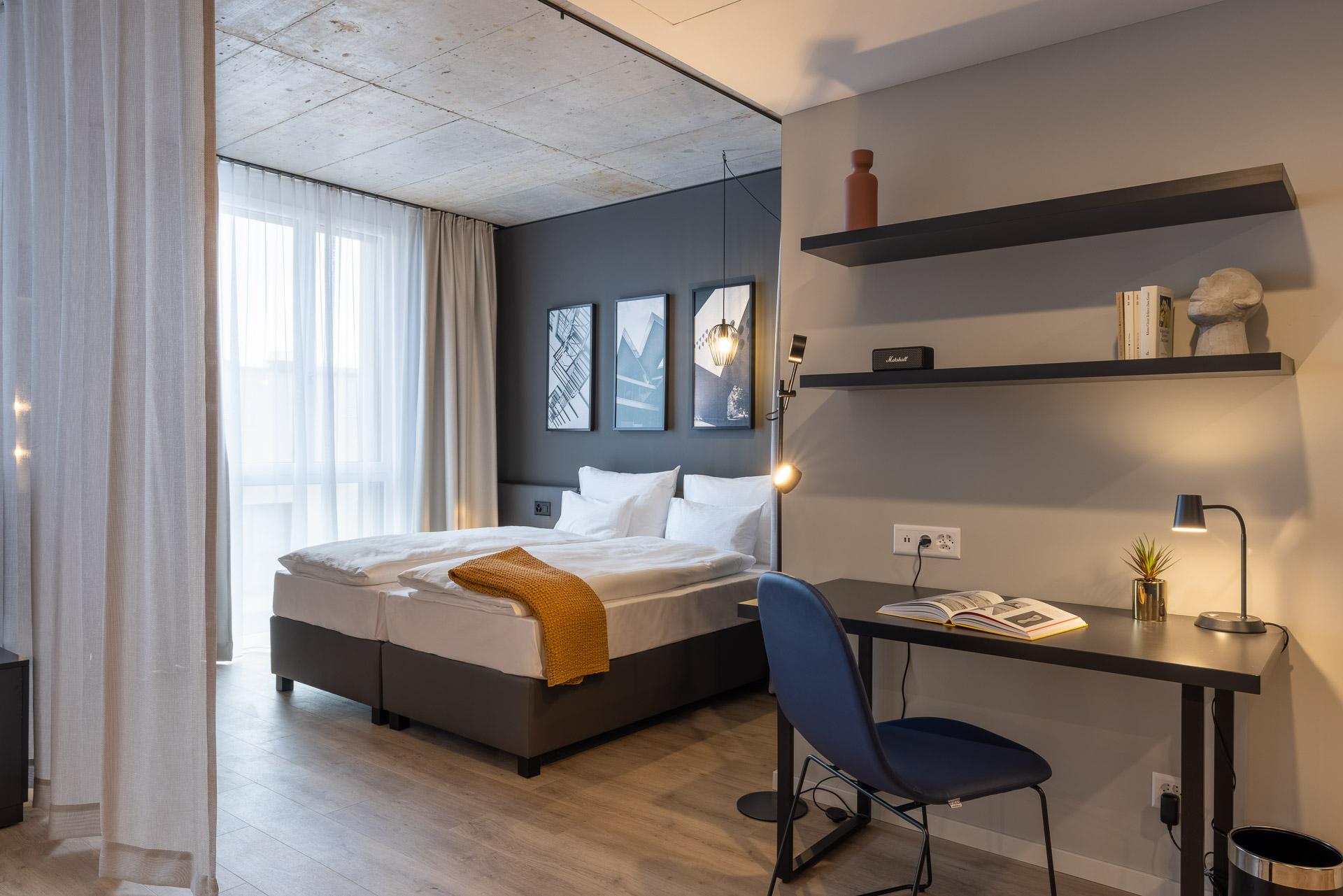 Blick auf das Bett mit Leinenvorhang und Schreibtisch als Arbeitsplatz l