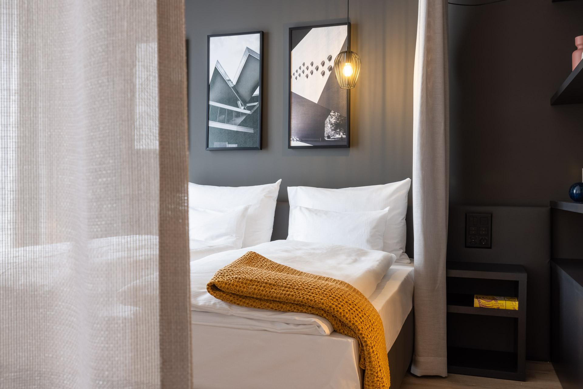 Blick auf das Bett mit Leinenvorhang als Detail