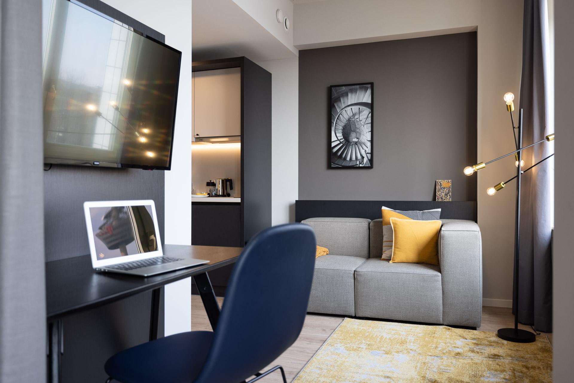Schreibtisch mit Stuhl und Laptop , Sofe mit gelben Kissen im Hintergrund