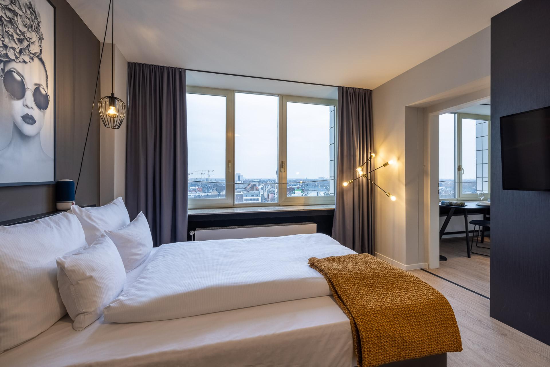 Blick auf Bett im Studio Apartment mit Skyline von Köln im Hintergrund
