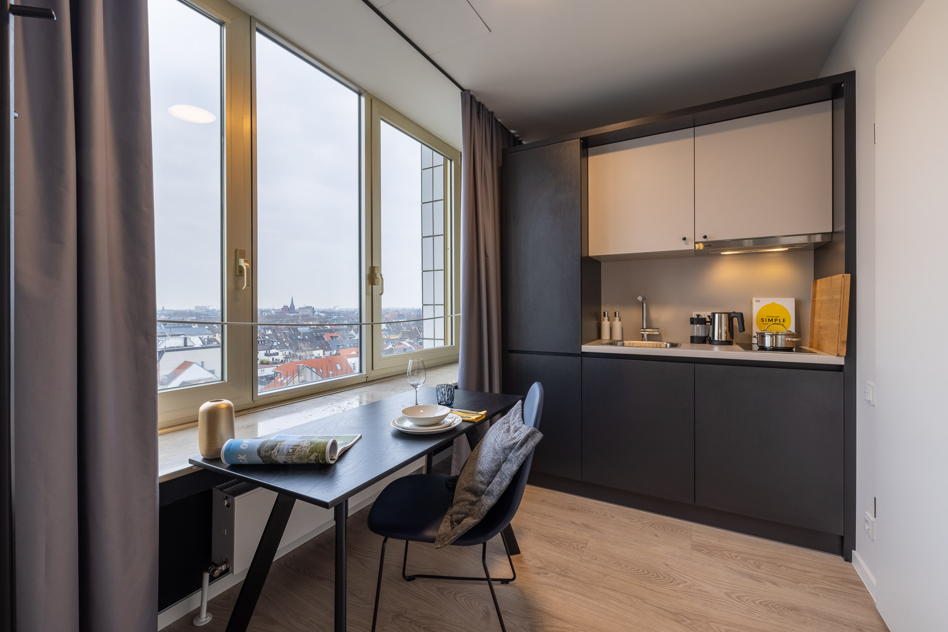 Schreibtisch mit Stuhl und Küche im Studio Apartment mit Skyline von Köln im Hintergrund