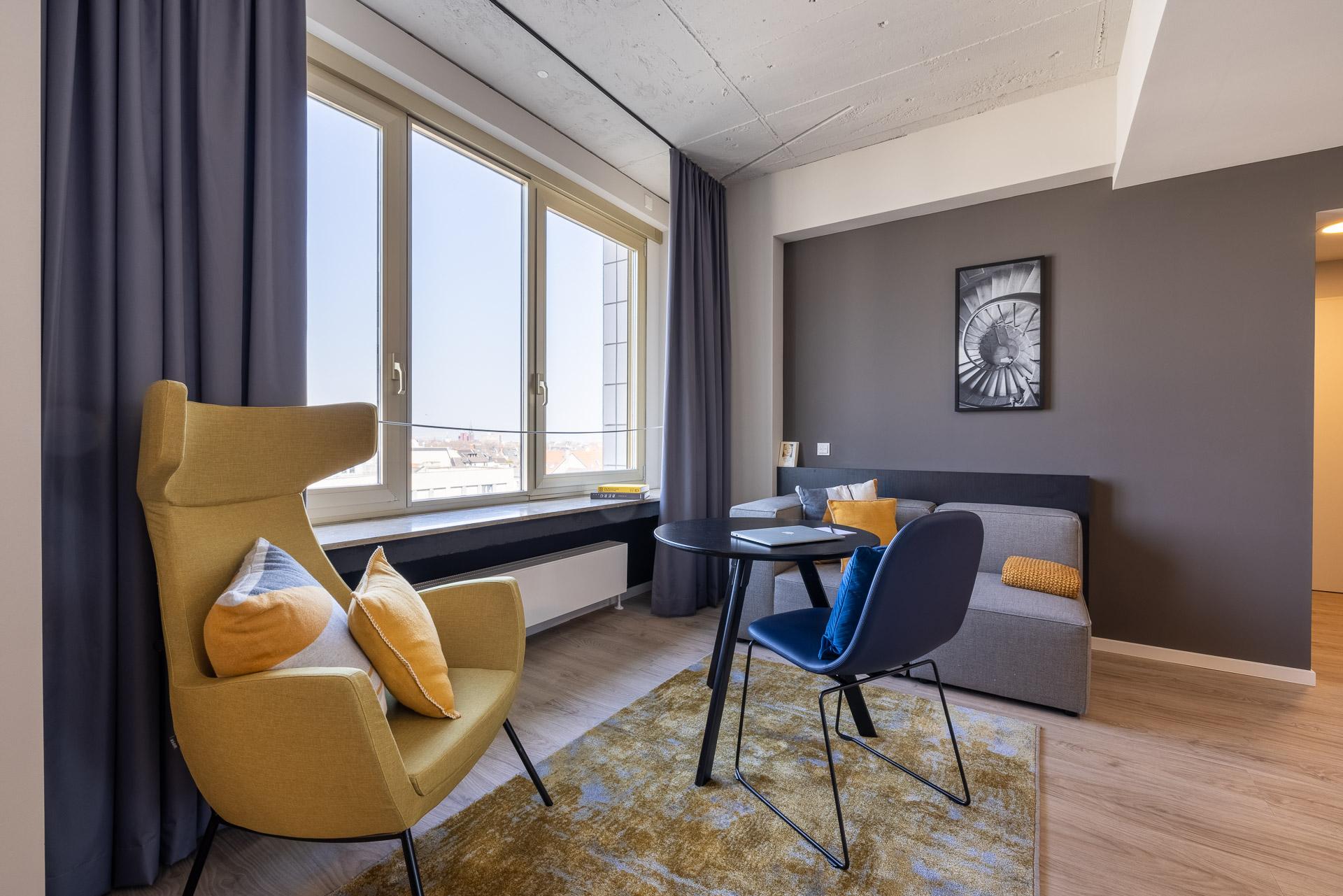 gelber Sessel, Tische und Sofa im Studio Plus Apartment mit Skyline von Köln im Hintergrund